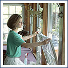 Woman opening a double-hung replacement window